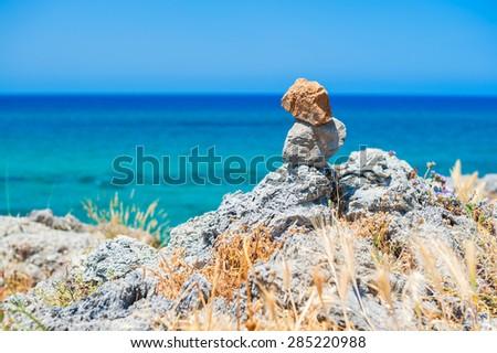 Stones balance on a rocky coast in the background of the sea. Crete island, Greece - stock photo