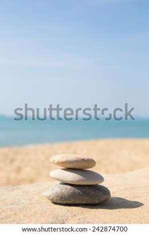 Stones balance, pebbles stack on the sand beach with shadow on right side , beautiful sea view during daytime on a sunny day with blue sky on background - stock photo