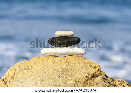 Stones balance, vintage retro instagram like hierarchy stack over blue sea background. Spa or well-being, freedom and stability concept on rocks.