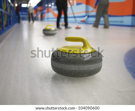 Stones for game in curling on ice. Playing people on the background. The concept - the productive leisure, a healthy way of life. - stock photo