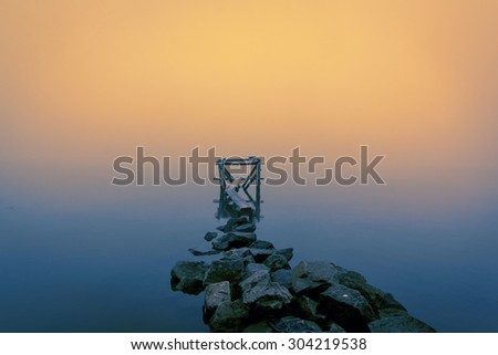 Stones gangway with wooden jetty in the autumn foggy river - stock photo