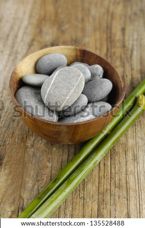 Stones in bowl with thin bamboo grove on wooden