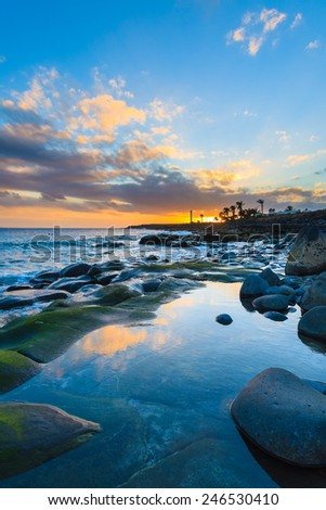 Stones in ocean water at sunset time in Playa Blanca on Lanzarote island, Spain  - stock photo