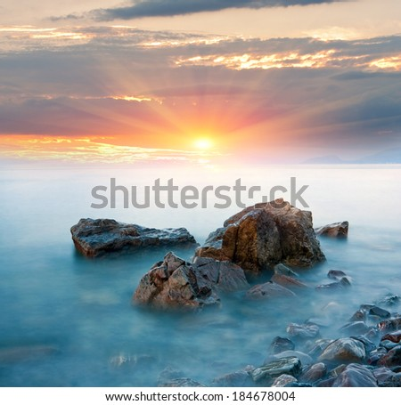Stones in sea water on sunset background - stock photo