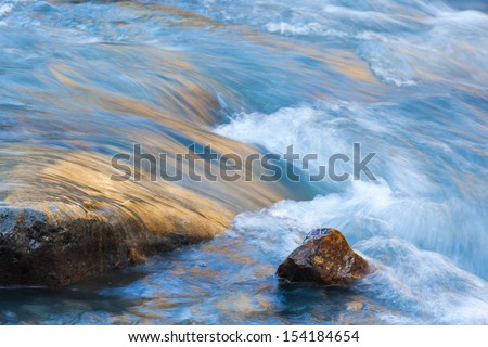 Stones in the flowing river - stock photo