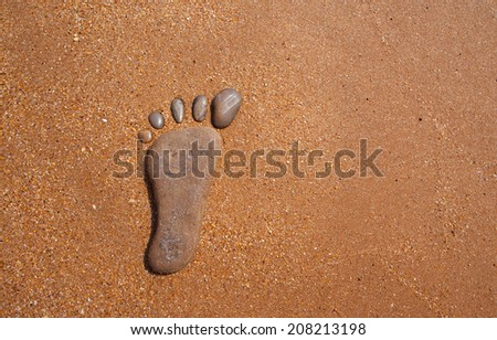 stones in the shape of feet representing footprint in the sand - stock photo