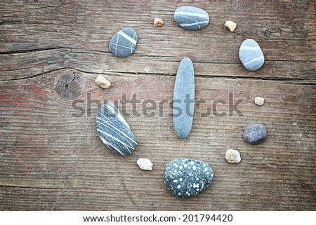 stones on a wooden background, the concept of equilibrium The burden hours - stock photo