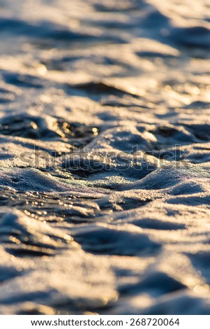 Stones on beach and sea water in sunset light - stock photo