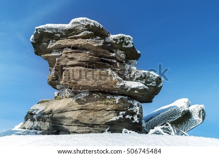 Stones on Mountain Peak Covered with Frost and Blue Sky
