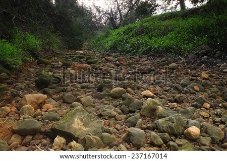 Stones on the river bed. Photograph taken in Algarve, Portugal - stock photo