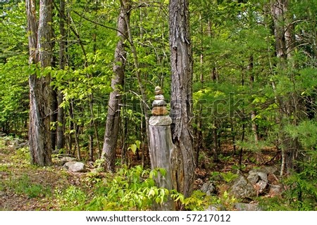 Stones piled into a cairn on a stump at the side of a Maine country road. - stock photo