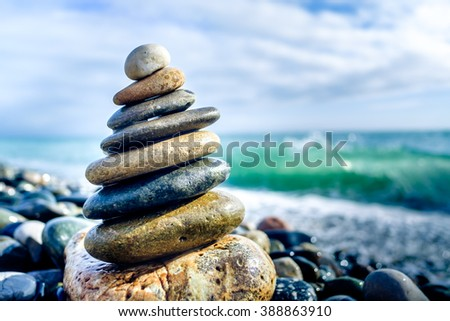 Stones pyramid on pebble beach symbolizing stability, zen, harmony, balance.