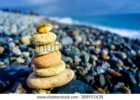 Stones pyramid on pebble beach symbolizing stability, zen, harmony, balance. Shallow depth of field. - stock photo