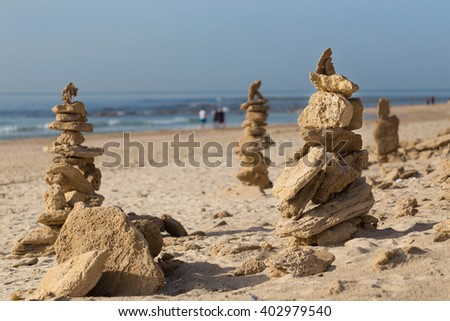 Stones pyramid on the beach with sea on the background. Symbol of zen and meditation.  - stock photo