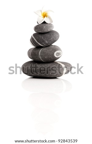 Stones pyramid with a plumeria flower, isolated on white background