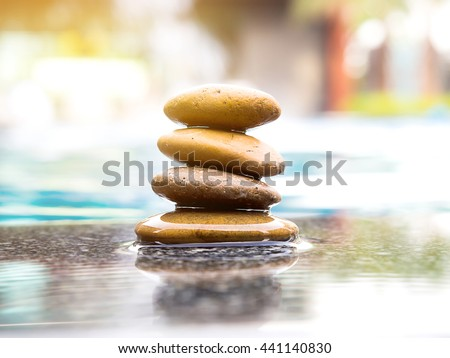 Stones pyramid with swimming pool blur background and sunlight. Photo of symbolizing zen concept. - stock photo