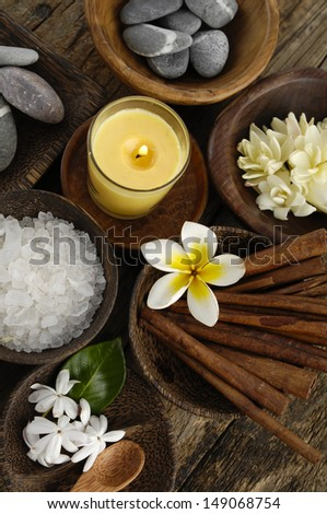 Stones, soap, salt, cinnamon, frangipani salt in bowl on old wood