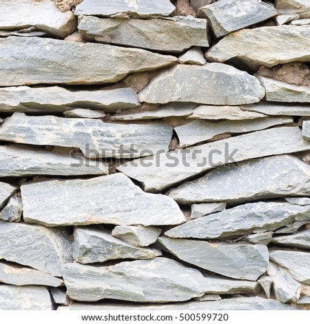 stones were arranged in a wall. Stones of various sizes that are arranged in a wall.