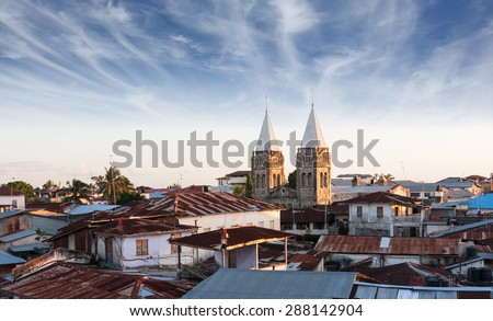 stonetown zanzibar roof-top view over city showing rusted zinc roof's and church spires - stock photo