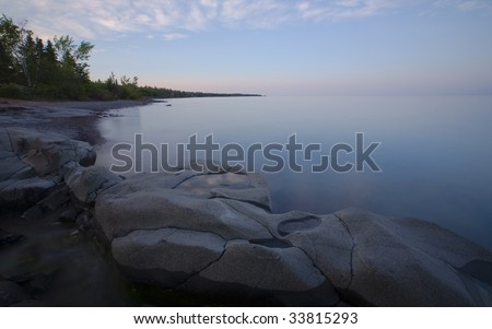Stoney Point Pensieve - clouds reflecting in a small rock on the North Shore of Lake Superior in Minnesota - stock photo