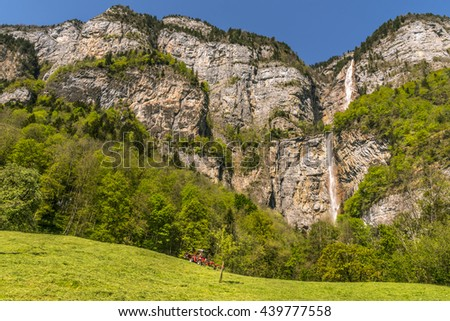 Stony Alps mountains and a tall waterfall -  Spring scenery with the cliffs of the swiss Alps garnished by green forests. From its peaks falls the Seerenbach cascade, near Betlis, Switzerland.