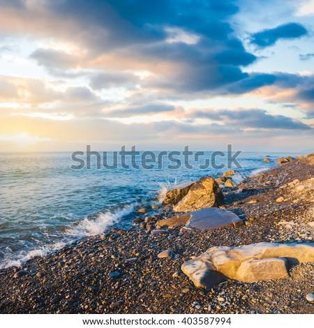 stony sea coast at the sunset - stock photo