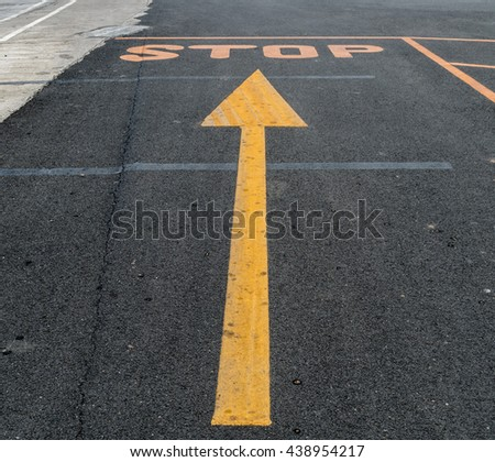 Stop and arrow traffic sign on asphalt road