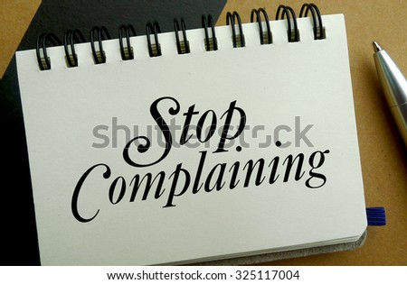Stop complaining memo written on a notebook with pen