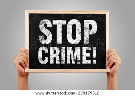 Stop Crime blackboard is holden by hands with gray background. - stock photo