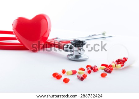 Stop disease. Close up of pills spread over the table with stethoscope and heart lying beside. - stock photo