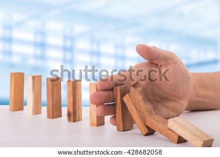 Stop domino risk effect ,businessman using hand for management solution. - stock photo