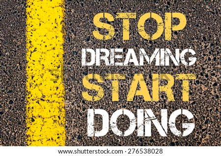 Stop dreaming start doing motivational quote. Yellow paint line on the road against asphalt background. Concept image - stock photo