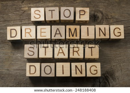 Stop dreaming. Start doing. Motivational text on a wooden background - stock photo