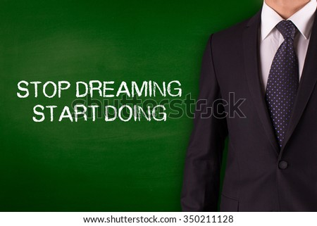 STOP DREAMING START DOING on Blackboard with businessman - stock photo