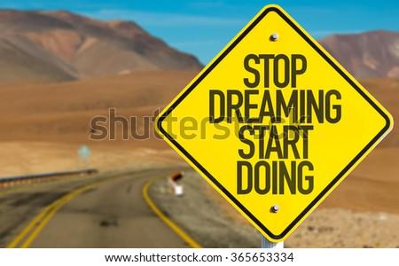 Stop Dreaming Start Doing sign on desert road - stock photo