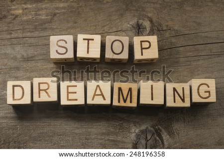STOP DREAMING text on a wooden background - stock photo