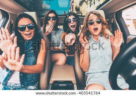 Stop! Four young women gesturing and looking terrified while sitting in car together - stock photo