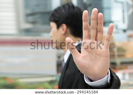 Stop gesture, side view of Asian businessman standing in the city. - stock photo