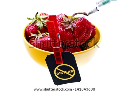 "Stop GMO concept shot. Genetic food engineering concept with a fresh red strawberry in a yellow plate, syringe with capsules and ""Do not disturb"" label on a clothespin/Strawberry genetic modification - stock photo"