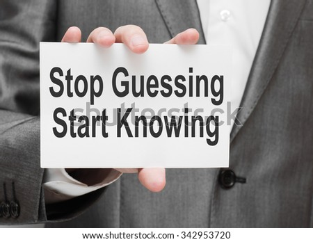 Stop Guessing, Start Knowing. Businessman holding a card with a message text written on it - stock photo