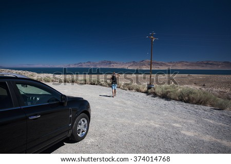 Stop over on a rental SUV car road trip, tourist enjoying the desert view and mountains, wild west landscape in Nevada, USA - stock photo
