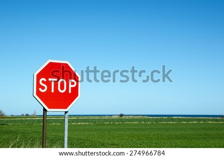Stop roadsign by a green field with blue water in the horizon - stock photo