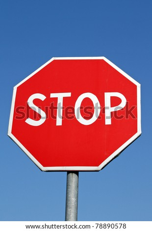 Stop roadsign over clear blue sky - stock photo