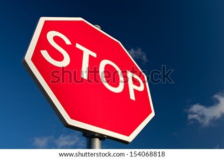Stop sign against deep blue sky. Close up. - stock photo