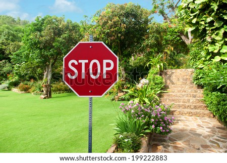 Stop sign against Natural stone landscaping in home garden with stairs during summer time