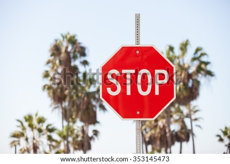 Stop sign against palm trees and sky