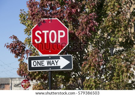 Stop sign and one way sign against a tree in the autumn