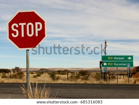 Stop sign and road sign on R31 highway in Kuruman in the Northern Cape region of South Africa. July 24th 2017.