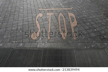 stop sign and waterspout on floor at a car park area - stock photo