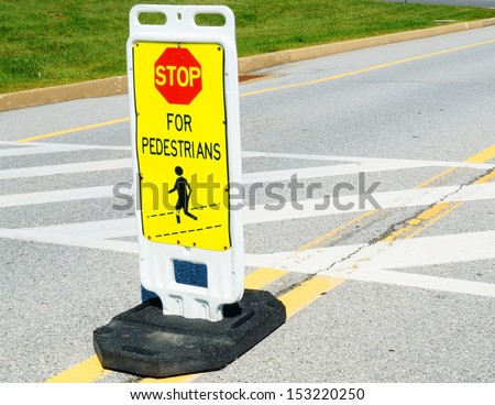 Stop Sign at Pedestrian Crossing.  A stop for pedestrians sign marks a crosswalk in the street.